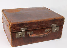 Old leather suitcase around 1900 with various travel accessories