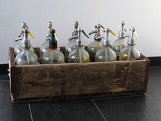 Ten glass spray bottles in wooden crate.
