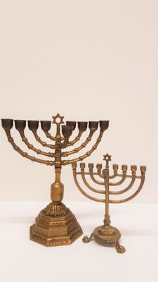 Two brass menorahs with the star of david