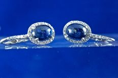 2 magnificent natural translucent sapphires in oval cabochons, each 1.55 ct, mounted in 18 kt white gold earrings, surround and hook in brilliant-cut diamonds totalling 0.39 ct - length 2 cm.