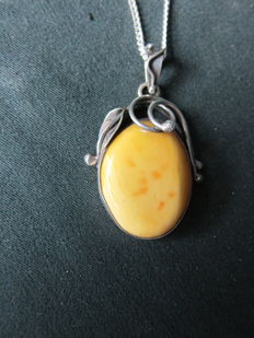 Silver Art Nouveau necklace with a cabochon cut amber stone, around  1920.