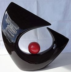 Abstract sculpture of ceramic, black with a red ball