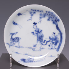 "Beautiful, fine, blue white porcelain plate, ""lange lijs"" (tall, slender female figure), fool and deer - China - 18th century (Yongzheng period)."