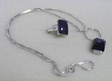 A silver link necklace and quartz pendant with a silver ring that has a huge glitter quartz