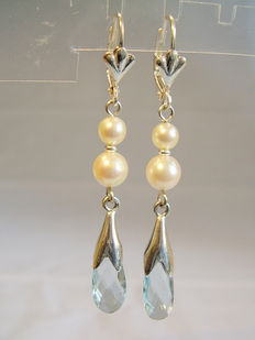 Earrings with authentic blue topazes and white Akoya pearls.