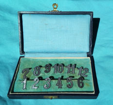 Twelve silver art deco table numbers in case, ca. 1920 / 12 CONTINENTAL SILVER NUMBERS, PLACE NUMBERS or DRINK MARKERS from the ART DECO PERIOD