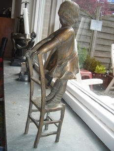 Bronze sculpture of a girl standing on chair