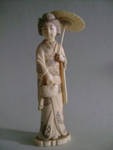 Ivory Okimono. Young geisha with an umbrella and bag - Japan - ca.  1900.