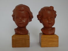 2 children's heads on a wooden base.