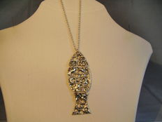An antique silver pendant in a stylised fish shape on an inheritance necklace