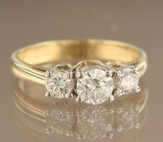 14 kt bi-colour gold trilogy ring set with brilliant cut diamonds, centre stone examined by IGI, ring size 17.5 (55)