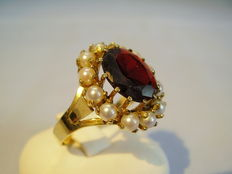 A gold ring with a big garnet of 5 ct and a pearl entourage