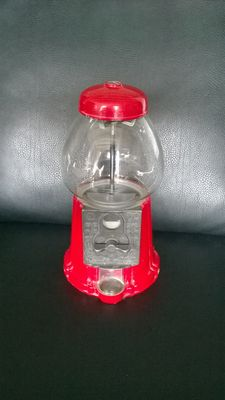 Vintage red chewing gum machine made of metal with glass dome in good condition