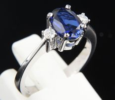 14 kt white gold ring set with a central, oval cut sapphire, approx. 1.60 carat in total and two brilliant cut diamonds, 0.12 carat