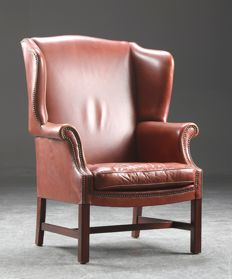 A brown leather wing armchair, second half of 20th century