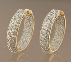 Bi-colour, 14 kt gold creole earrings set with 260 brilliant cut diamonds, approx. 1.30 carat in total.