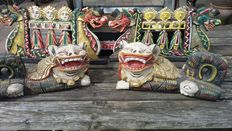 Two wooden ornaments with dragons at the side. And two wooden temple lions.