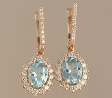 Rose gold dangle earrings of 14 kt, set with a central blue topaz and 48 brilliant cut diamonds, height: 2.6 cm, width: 1.0 cm
