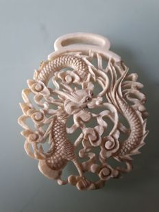 A carved pendant of a dragon in bone - China - second half 20th century