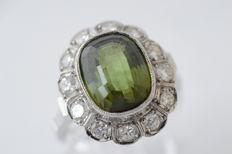 14 kt white gold entourage ring with peridot, approx. 3.00 ct and brilliant cut diamonds, approx. 0.50 ct – Ring size: 55.5 (17.75 mm).