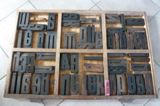 Old industrial typecase from a printing drawer of a printing company, with approximately 65 original block letters and numerals.