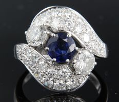 Platinum ring centrally set with a brilliant cut sapphire and two brilliant cut diamonds, 1.00 ct, surrounded by many brilliant cut diamonds of 1.80 ct, ring size 17.5 (55)