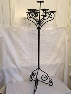 Sturdy nine-armed wrought iron candle holder.