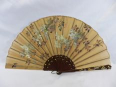A carved and parcel gilt wood folding hand fan - with hand painted motifs onto organza - Spain - circa 1900