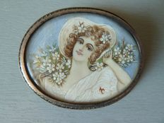 Romantic solid silver brooch with a signed miniature, showing a young woman in a hat, surrounded by flowers.