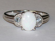 14 karat white gold ring with an oval, cabochon cut opal and two light blue topazes Ring size: 17 mm
