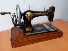 Antique Singer sewing machine with wooden cover, 1895