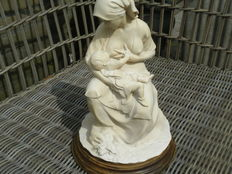 Sculpture made of polystone depicting a woman breastfeeding a baby.