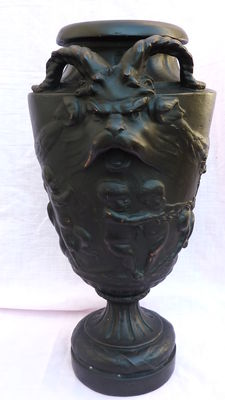 Vase in earth covered with a sheet of copper painted in black, with decoration of putto playing, two goat heads and bay leaves, late 19th century