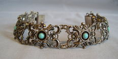 Silver bracelet with turquoise cabochons.