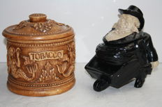 Two antique tobacco jars. One is in the shape of a man with a wheelbarrow and one decorated with mermaids. First half of 20th century, Belgium.