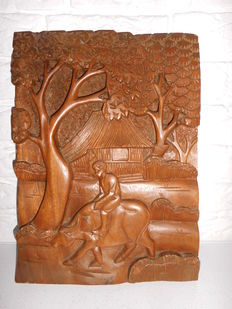 Wooden wall panel in relief with a boy on an ox - Bali - Indonesia.