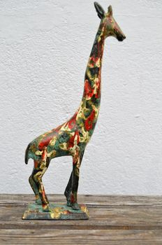 Colourful enamelled-painted bronze statue of a giraffe.