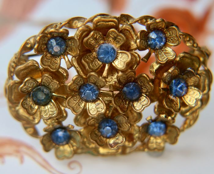 Antique gold plated broche with a peculiar flower design from around 1890with light blue for sale