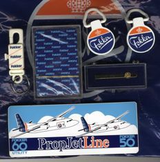 Fokker - various collectables (promotional gifts): tie pin, card game, key ring, labels, sticker, plastic bag (7 itemms)