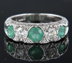 White gold ring of 14 kt, set with 3 brilliant cut emeralds of 1.00 ct ,2 brilliant cut diamonds of 1.20 ct and 8 diamonds of 0.03 ct, ring size: 17 (53)