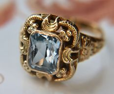 14 ct gold ring with a natural Topaz (2.08ct) in light blue color on a large open richly decorated frame work ringhead and an open rail