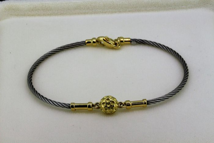 Cable-shaped bracelet in steel and 18 kt gold, measurements: 6.5 x 5 mm.