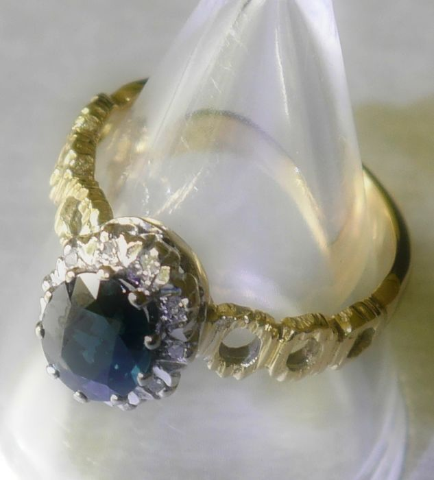 18 kt gold ring with sapphire surrounded by 10 diamonds