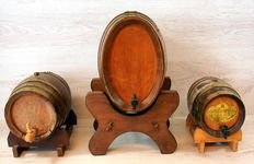 Three wooden mini wine barrels on standard