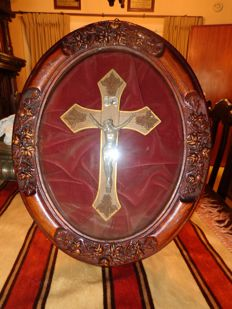 Wooden oval spherical frame with crucifix on velvet