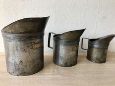 Three pieces antique calibrated measuring cups.