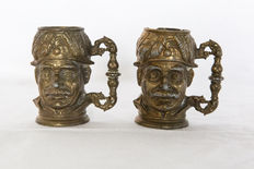 "Two miniature brass ""Character mugs"""
