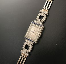 Women's Art Deco wristwatch made of 18 kt gold and platinum decorated with diamonds and calibrated harlequin cut sapphires