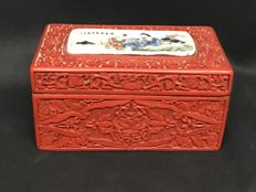 Box in red engraved lacquer, decorated with ceramic depicting people in a landscape – China – Second half of the 20th Century