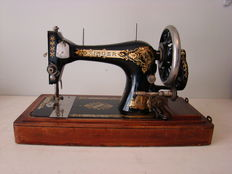 Singer 28 sewing machine with wooden dust cover, 1906.